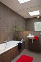 Red accents in a modern bath with a full wall mirror above the sink and brown tiles on the wall and floor