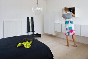 Lady in front of white floating cabinets in a minimalist bedroom and chartreuse dress on a black coverlet