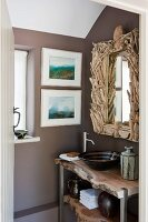 Rustic washstand under bathroom mirror with artistic driftwood frame; two modern watercolour landscapes on wall to one side