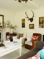 Scatter cushions on armchairs, white-painted wooden table, sofa and pictures with hunting motifs and antlers in living room