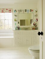Bright bathroom with white furnishings, wall mirror surrounded by bunting and white wooden floor