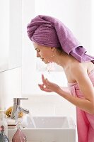 Woman wrapped in bath towel with towel turban on head washing in bathroom