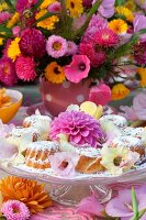 A brightly coloured summer bouquet behind a cake stand laden with freshly baked cakes and a magnificent dahlia