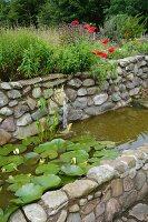 Wasserbecken aus Naturstein mit Terrakotta-Tierkopf als Wasserspeier und blühenden Seerosen