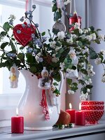 Baubles on branches of snowberry bush in white vintage pitcher and lit candles on window sill