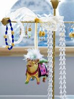 Metal animal figurine hanging on jewellery stand next to earrings and necklaces
