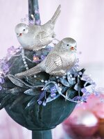 Metal bauble decorated with shiny silver bird figures and beads