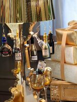 Bottle-shaped ornaments hanging from brass lampshade of standard lamp next to stack of presents