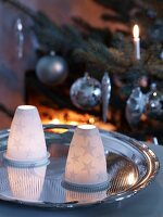 Tealights under porcelain covers with star motifs on silver tray in front of Christmas tree