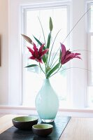 Pink lilies in glass vase and Japanese dishes on bamboo runner in front of window