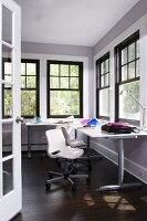 Modern workspace in corner of room with black, traditional lattice windows