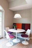 Classic, white plastic chairs at round table and built-in bench with striped cover in modern ambiance