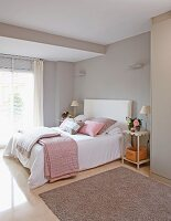 Double bed with blankets and scatter cushions in pastel grey and pink in bedroom with grey walls