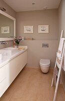 Narrow bathroom with long washstand unit, ladder towel rack and walls painted a warm grey