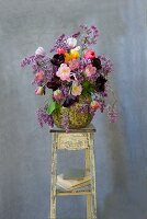 Summer bouquet with tulips and lilac in a vase on a flower stand