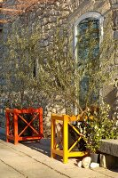 Colourful wooden frames around potted olive trees in front of stone house