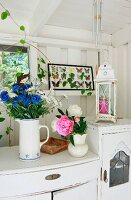 Bouquets on white chest of drawers in white wooden veranda