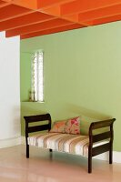 Orange-painted, wood-beamed ceiling above recamier against green wall