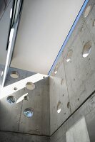 Light and shadow play in a shaft with circular holes in an exposed concrete wall
