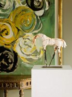 Cracked sculpture of a horse on pedestal in front of abstract painting; antique brass console table in background