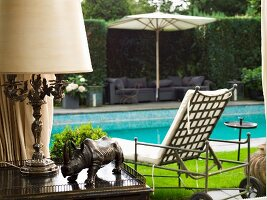 Rhinoceros sculpture and antique table lamp on side table; view of pool and elegant lounger in background