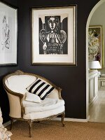 Rococo-style armchair with pale upholstery in corner of black-painted room below framed Picasso woodcut
