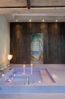 Floating candles in sunken bathtub, mural in background seen through doorway in rustic wooden wall