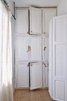 White lacque, r built in cupboard with natural wood door pulls in a narrow room