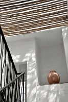 Sun filtering through a bamboo roof in a stairwell and view of an amphorea in a wall niche