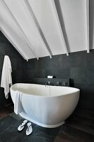 Freestanding bathtub in a modern bathroom with slate tiles on the wall and floor under a wood ceiling painted white