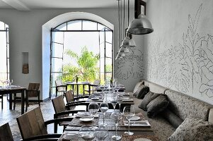 Set table and cozy bench seat in a restaurant with open terrace doors and view of trees in the courtyard