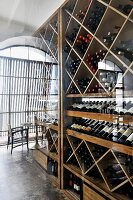 Wine cellar in tall, wooden wine rack and seating area in front of industrial, arched windows in a hall