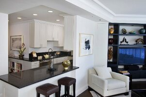Armchair with pale upholstery next to breakfast bar in front of open-plan kitchen