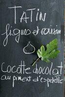 Hand-written menu and fig leaf on blackboard in kitchen