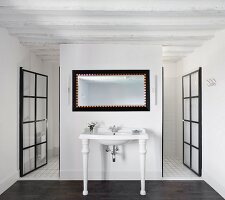 White vintage washstand against partition flanked by open glass doors with black metal lattice frames