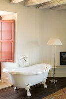 Free-standing vintage bathtub and classic standard lamp in corner of room with rustic ambiance