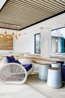 Covered terrace with a nautical armchair made from white lacquer, wooden rods