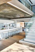 Galley kitchen under exposed concrete ceiling and free standing stairs with glass banister in an open living room