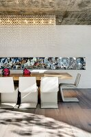 Designer dining area with cantilever chairs at a long table and mirror strips on the back wall; decorative lighting from the exposed concrete ceiling