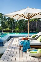 Cushioned sun loungers and sun umbrella on a wooden deck by a swimming pool