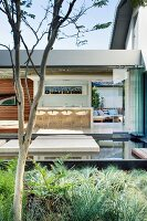 View across a planting bed and water feature through open folding doors into a one story building with a kitchen bar