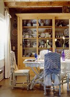 Chairs with fabric draped on backs around dining table in front of dresser full of crockery