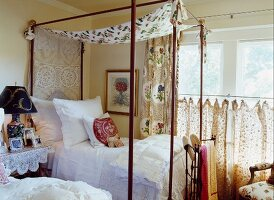 Delicate four-poster bed next to window in country-style bedroom