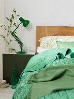 Bed with a wooden headboard and plaid pattern next to a night stand with a green, retro table lamp