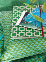 Postcards and folder on pillows and blue and green plaid pattern