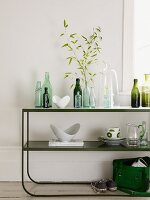 Bottles and crockery on retro shelves made from curved metal in front of a white wall
