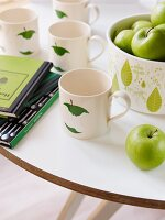 Cups with apple decor next to a bowl with green apples on a white table