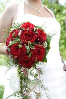 Bride holding bridal bouquet of red roses