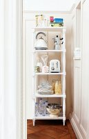 Kitchen utensils on white-painted wooden shelving in corner of room with traditional elements