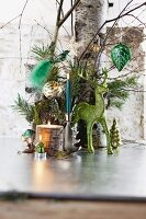 Green reindeer ornament and lit candle in front of tree trunk decorated with Christmas baubles